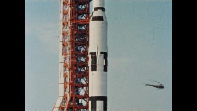 1960s: Helicopter takes off and flies away from launch pad with rocket on it. Rocket sits on launch pad.