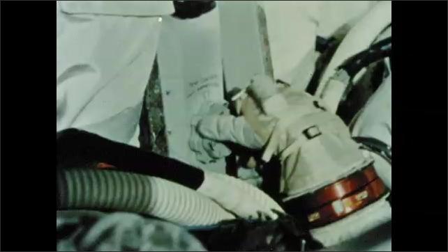 1960s: Astronaut in cockpit of simulator. Astronaut works control panel then checks helmet. Astronaut walks in spacesuit.
