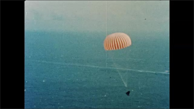 1960s: View of parachute from Gemini space craft window. Command module descends toward ocean with parachute. Men on helicopter look out of window.