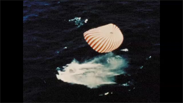 1960s: Command module descends toward ocean with parachute. Command module splashes down in ocean. Navy seals jump into ocean from helicopter hanging over ocean.