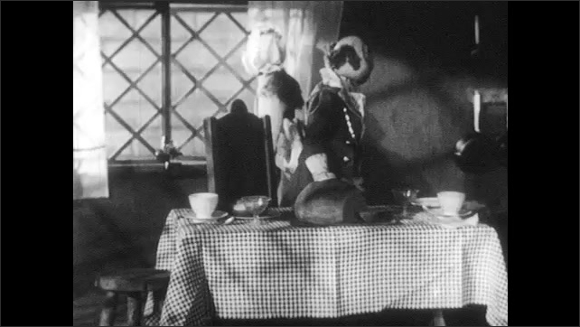 1940s: Man puppet sits at table, looks grumpy, talks. Woman puppet walks to window, man stands up looks out window. Woman opens window, turns around, talks to man.