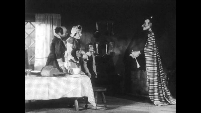 1940s: Puppet family stands together in kitchen, piper puppet walks to them. Piper talks to family.