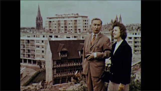 1960s: Man and woman on hill above city, stop and talk.