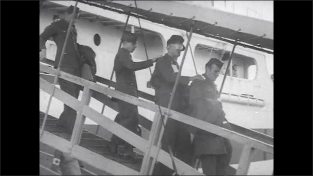 1940s: Medics carry injured soldiers over gangplank from boat. Injured soldiers walk with hands on each other's shoulders from boat. Soldiers walk down gangplank from boat.