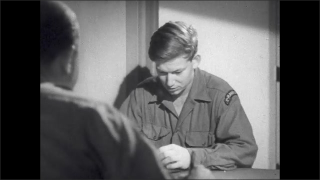 1940s: Soldier sits at table talking to psychiatrist.