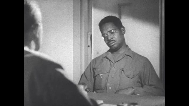 1940s: Soldier sits at table talking to psychiatrist. Different soldier sits at table talking to psychiatrist.