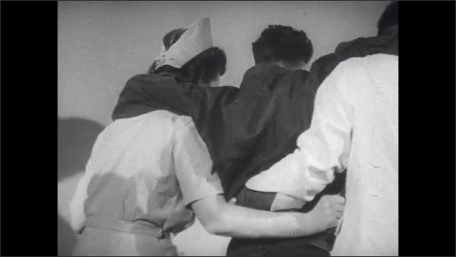 1940s: Nurses walk feeble patient down hall, propping his arms over their shoulders and then sitting him onto bed.