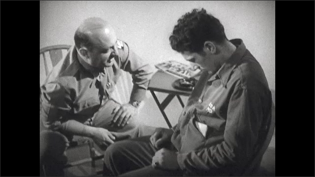 1940s: Therapist sits and talks to a man who sits with his head low and his hands on his lap. A man with his face held low.