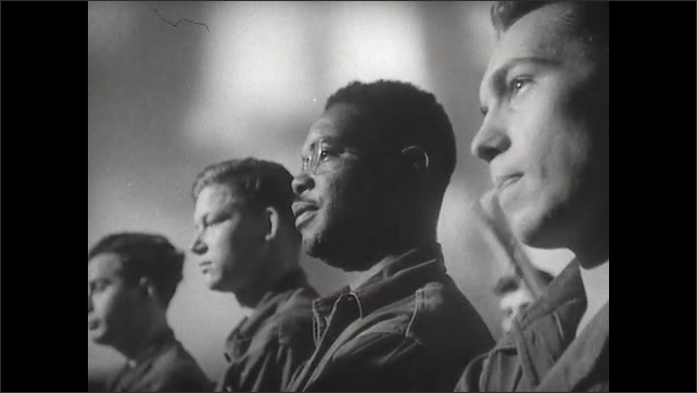 1940s: UNITED STATES: man in uniform talks to soldiers in church. Men listen to talk. Side profile of man's face