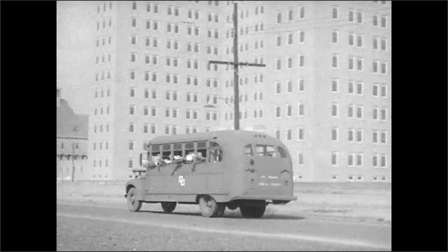 1940s: UNITED STATES: nurses wave at soldiers. Soldiers wave from bus. Bus leaves military hospital.