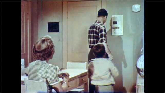 1950s: Boy stands in kitchen, woman looks at sleeves of boy's jacket. Man enters kitchen, boys shows man jacket sleeves. Man and woman talk, man gets board out of closet.