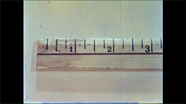 1950s: Man and boy walk over to kitchen table, join woman, look at ruler. Man uses pen to point at numbers on ruler, points at distance between numbers.