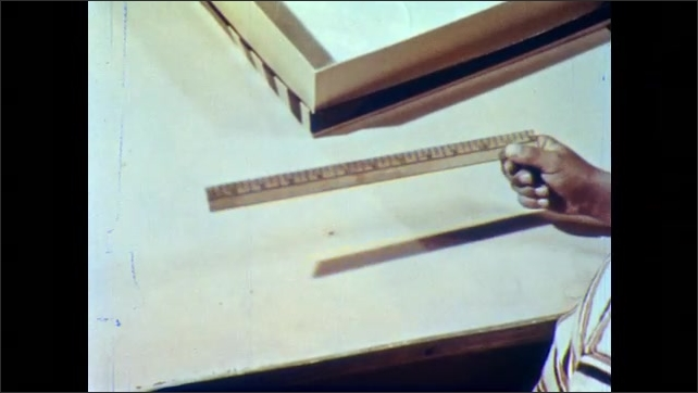 1950s: Man and boy stand over kitchen table, look at ruler, talk. Boy picks up ruler, man walks to closet, woman talks to boy. Man brings yardstick out of closet.