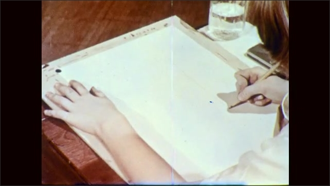 1950s: Girl at classroom desk carefully sketches on paper to begin a painting. Boy in desk next to girl also sketches.