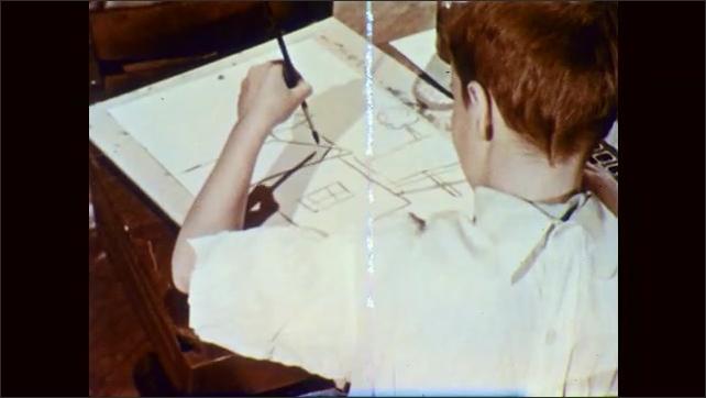 1950s: Boy at classroom desk paints on paper. Classmates paint at desks. Boy paints a house on paper. Hand sketches leaves on paper.