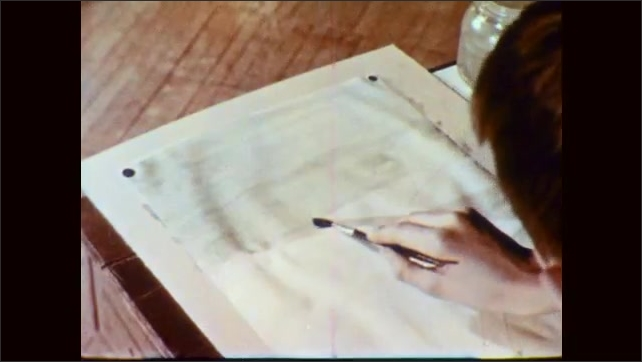 1950s: Students paint at desks. Hand washes blue paint on sheet for sky composition.