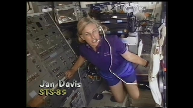 1990s: Astronauts speak in cabin.  Space shuttle.  Robotic arm moves.