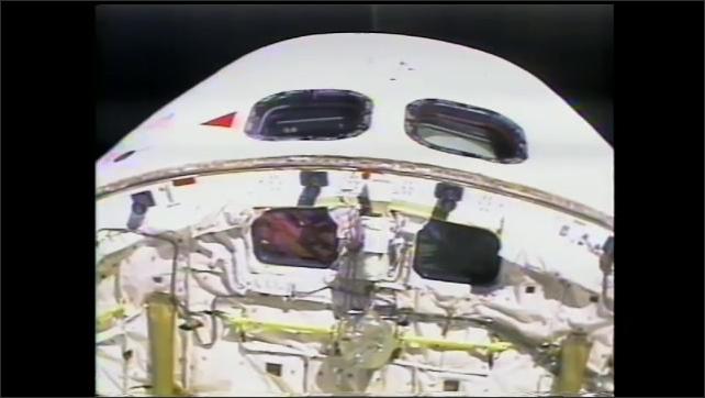 1990s: Astronauts work outside space shuttle.