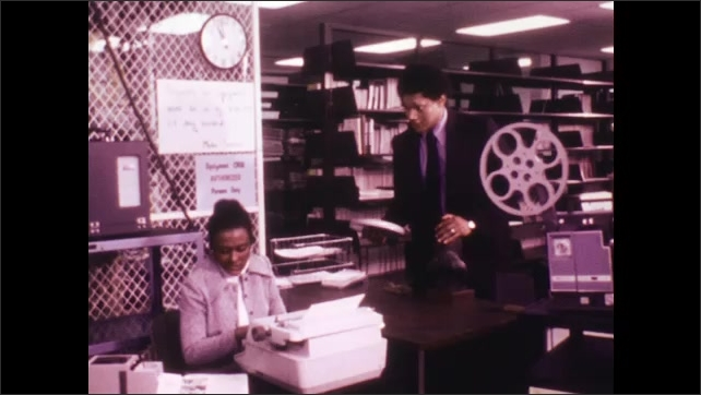 1970s: Woman in media room types on typewriter. Man with roll of film approaches woman and desk and talks to her.