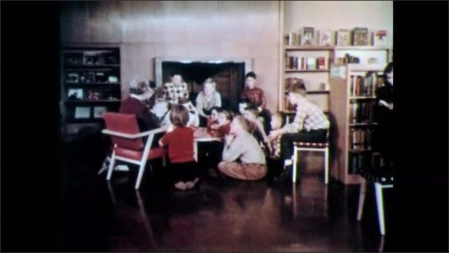 """1970s: Window is labeled """"THE CHILDREN'S ROOM.""""  Children sit at listen to story.  Girl walks past.  Girl sits at table and works."""