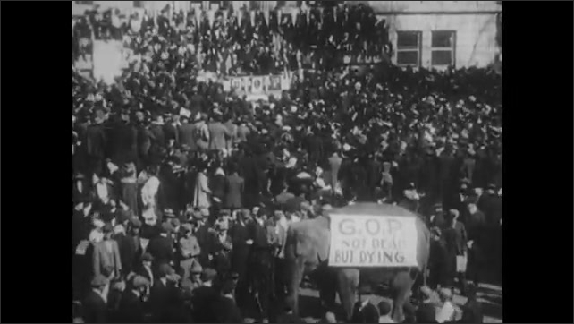 1920s: Parade.  Crowd.  Man waves hat from back of car.  Elephant wears sign.  Woodrow Wilson gives speech.