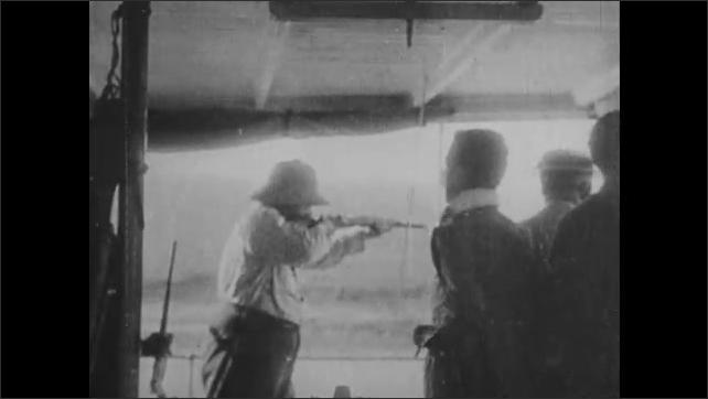 1920s: Jungle.  River.  Boat.  Alligators.  Man aims gun.