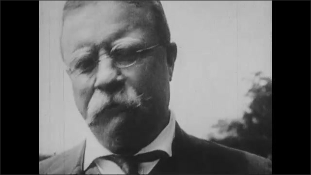 """1920s: Teddy Roosevelt gives speech to crowd.  Men clap.  Women march holding banner that reads """"WAKE UP AMERICA.""""  Newspaper headline reads """"WAR.""""  White House."""