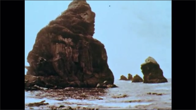 1960s: Large rocks on beach, exposed by low tide. Large rocks off shore as low level of waves wash around them to shore.