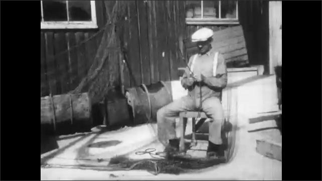 1940s: Hands fixing net, tilt up to man. Man fixing net. Men rolling barrels on dock. Truck drives past construction site.