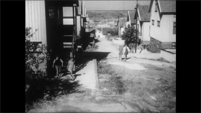 1940s: Man sanding plank. Low angle shot of men constructing roof. Children exit house, walk down street.