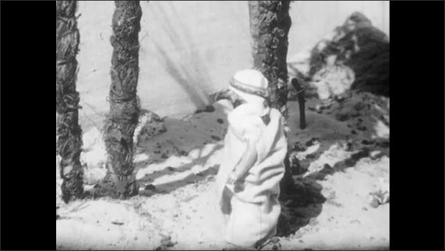 1940s: Boy picks up and turns male doll.  Model of desert.
