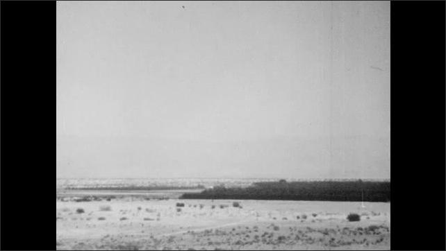 1940s: Desert.  Car drives down sand path.