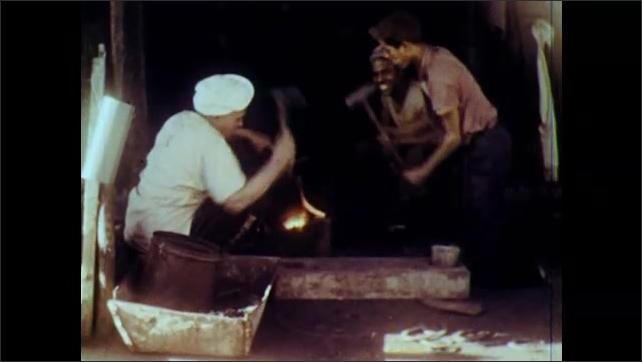 1960s: Men hammer hot metal.