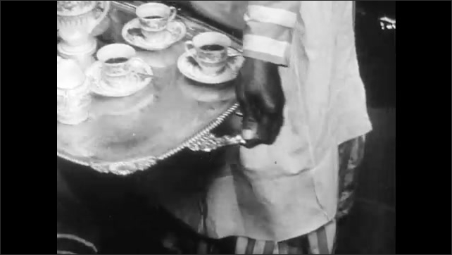 1940s: Servant offers tray of drinks to woman, woman spoons sugar into cup, takes drink from tray. Servant offers drinks to seated guests. Woman sits in room, plays harp.