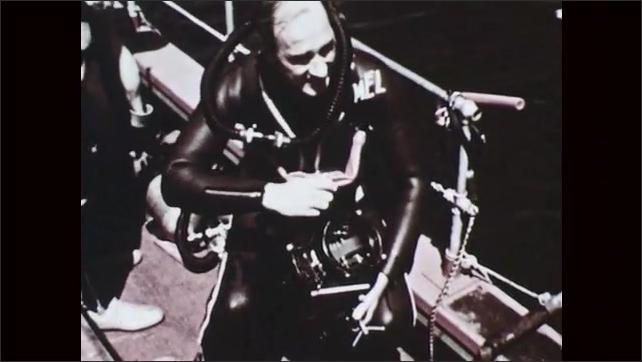 1950s: Underwater view of school of fish swimming near rocks. View of man in scuba gear on boat. Man adjusts helmet. Underwater view of many tiny fish swimming.