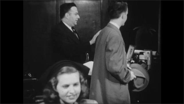 1940s: Woman talking, men in background stand, walk to door, shake hands.