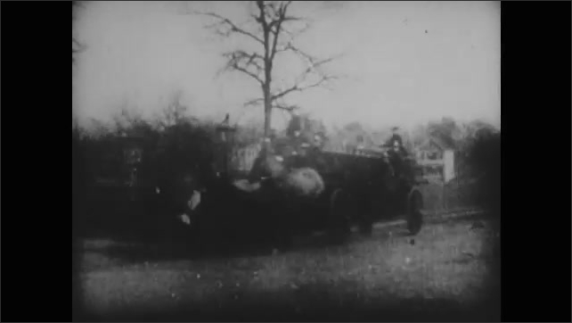 1900s: People stand on street.  Firemen pass in horse-drawn wagons.  Firemen move hoses through yard.  House.