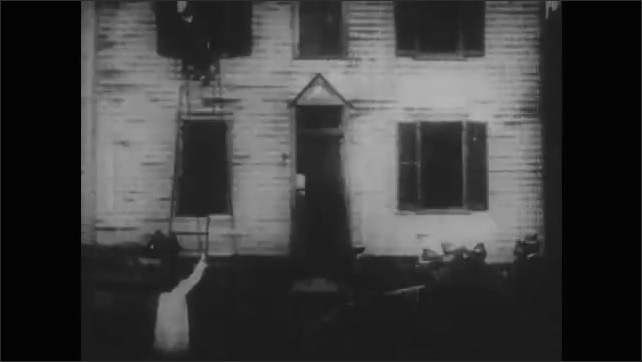1900s: Fireman rescues child from burning bedroom.  Man climbs down ladder.  Firefighters spray water into burning house.  Mother and child embrace.
