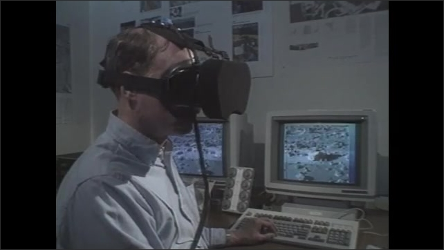 1990s: Man looks through virtual reality goggles in front of two computer monitors broadcasting what he's looking at. Looking around rocky planet terrain.