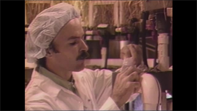 1990s:Scientists examine plants growing in chamber. Man examines wheat stalk and dispenses nutrient rich liquid for plants. Artificial sunlight is administered. Man watches on video monitor.