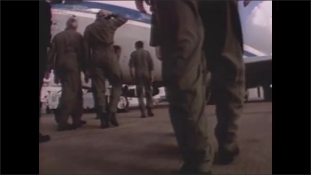 1990s:Man pulls out keyboard from computer bank and begins typing. People in flight suits walk towards airplane. Man in flight suit and mustache explains flight path.