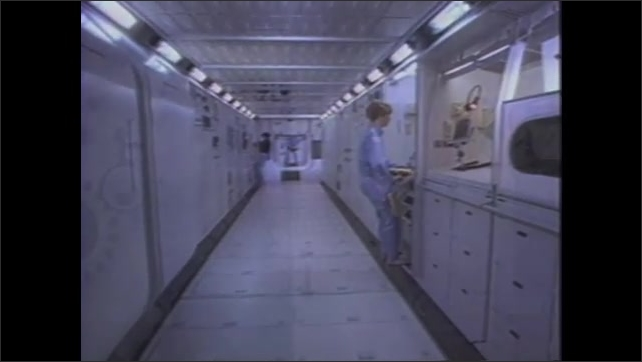 1990s:??Diver inside small, contained underwater space. Diver walks through hallway and another diver opens microwave.??