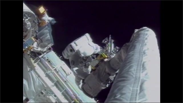 1990s: Astronauts work on equipment in space. Intertitle card.