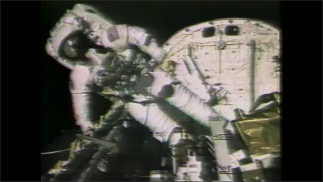 1990s: Intertitle card. Astronaut works on exterior of spacecraft.