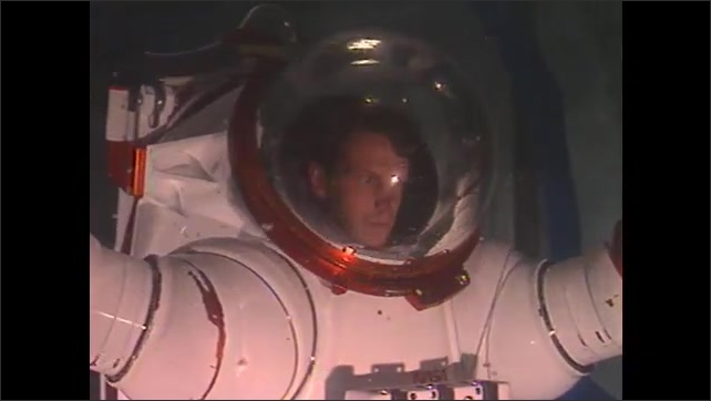 1990s: Man in test spacesuit walks and moves underwater.