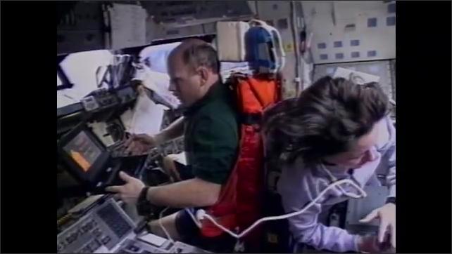 1990s: Hubble telescope. Astronauts work on hubble telescope. Astronauts inside space shuttle. Man inside test spacesuit moves arms.