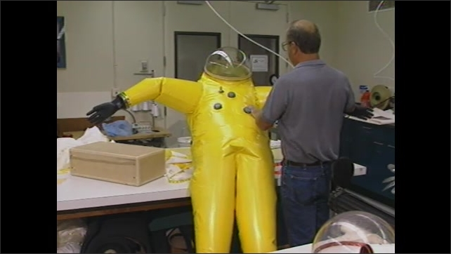 1990s: Chernobyl. Man examines and inspects safety suit.