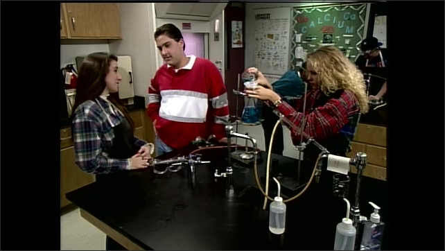 1990s: Students work on experiments in science classroom. Boy flirts with girl at lab station. Teacher looks up from papers and stands at desk. Feet walk around classroom. Boy flirts with girl.