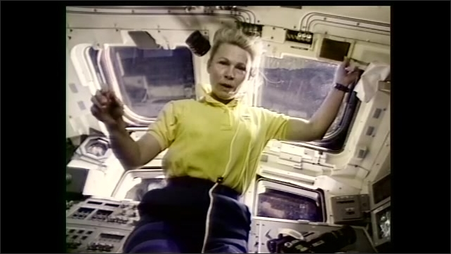 1990s: Teacher and students look at television and speak. Astronaut floats in space station and speaks through television. Students work on experiment at lag station table.
