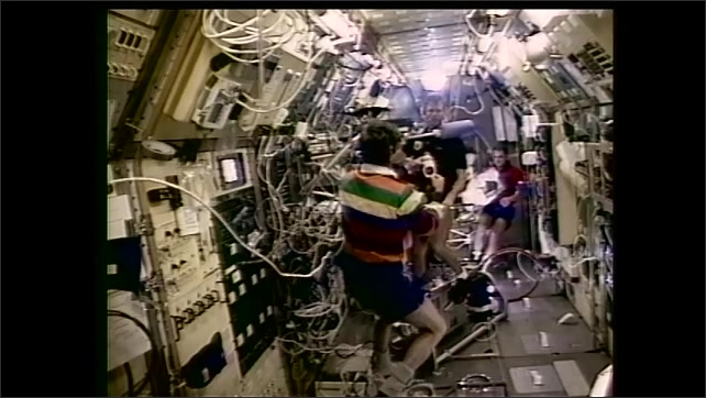 1990s: Astronaut floats toward man peddling exercise bike on Spacelab. Astronauts talk and float on space station.